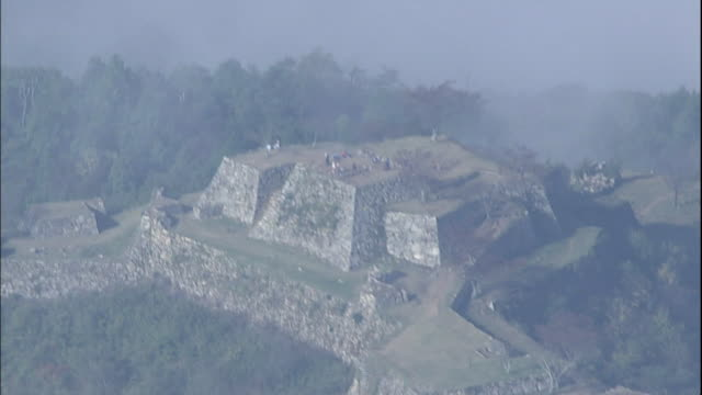 clouds surround the ruins of takeda castle constructed on a mountain in hyogo, japan. - 遺跡点の映像素材/bロール
