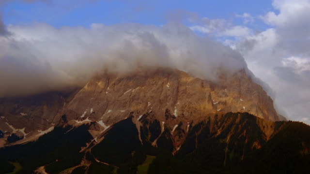 vídeos de stock, filmes e b-roll de clouds swirl around mount zugspitze in the bavarian alps. - montanhas wetterstein