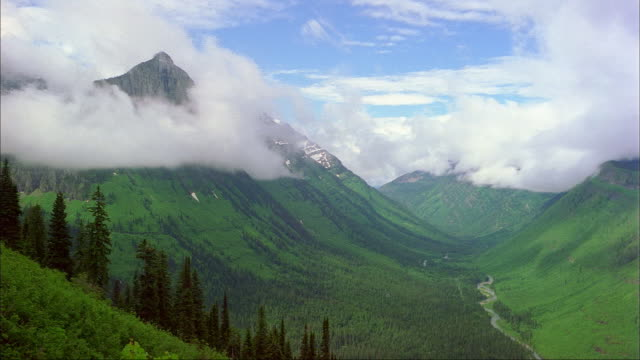 Clouds swirl over a valley in Glacier National Park.
