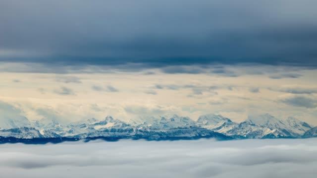 wolken wirbeln um schneebedeckte berge - zeitraffer - wind stock-videos und b-roll-filmmaterial