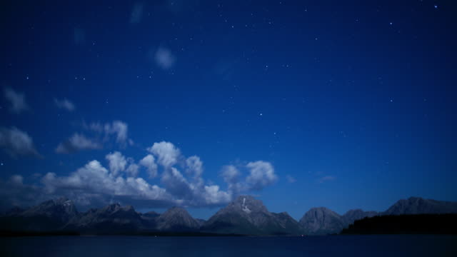 vídeos de stock, filmes e b-roll de clouds time lapse and and grand teton national park mountain lake at night - grand teton