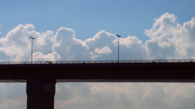 clouds with silhouette of the bridge and truck - trailer stock videos & royalty-free footage
