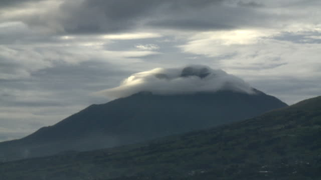 Clouds wrap around the top of a volcano in the Volcanoes National Park of Rwanda. Available in HD.