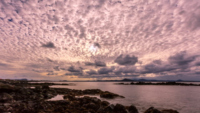 vidéos et rushes de cloudscape with 	altocumulus and basalt beach of udo island(travel destination) at sunset - altocumulus