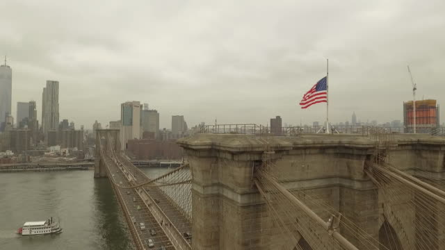 cloudy day drone footage up the side of the brooklyn bridge and above with the american flag flying also looking down across the bridge with new york... - brooklyn bridge stock videos & royalty-free footage