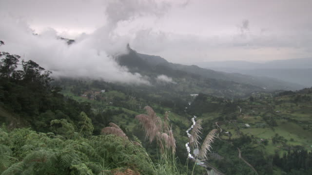 Cloudy forested valley with small river, fields and farms, rural Cundinamarca region, Colombia