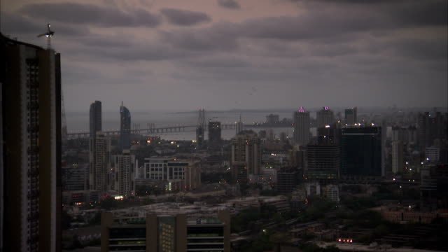 A cloudy sky outlines the Mumbai skyline in the golden hour. Available in HD