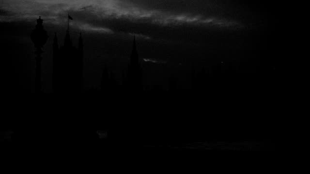 a cloudy sky outlines the silhouetted houses of parliament near river thames at night. - victoria tower stock videos & royalty-free footage