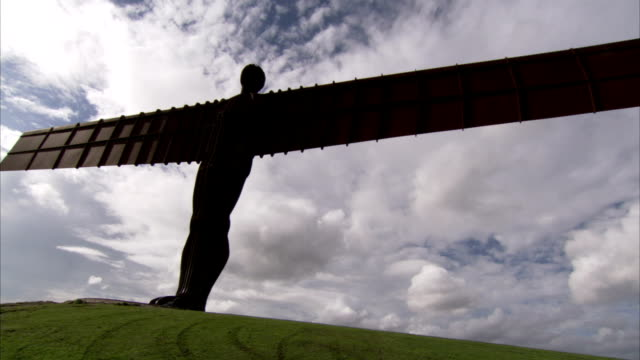 a cloudy sky silhouettes the dramatic angel of the north statue in gateshead, england. available in hd. - angel of the north stock videos and b-roll footage
