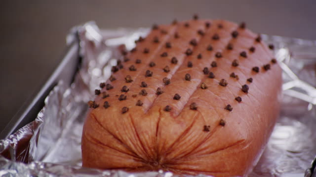 Cloves are placed into a large ham prior to baking.