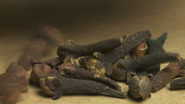 cloves dispersed on a wooden board macro - speisen stock videos and b-roll footage