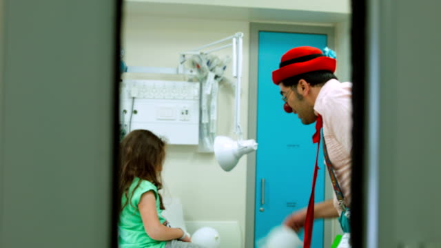 stockvideo's en b-roll-footage met clown  amuses the girl in hospital - menselijke neus