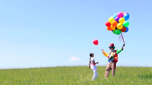 clown und mädchen mit luftballons auf feld - ganzkörperansicht stock-videos und b-roll-filmmaterial