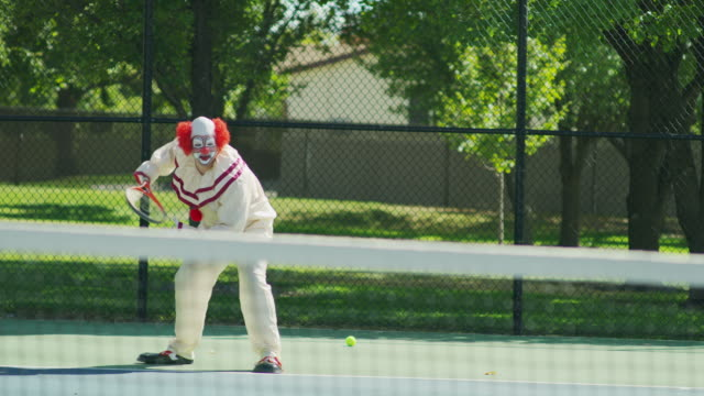 Clown awkwardly playing tennis and avoiding balls / Pleasant Grove, Utah, United States