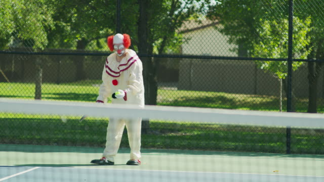 clown awkwardly serving tennis ball underhand / pleasant grove, utah, united states - clown stock videos & royalty-free footage
