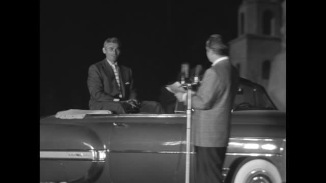 Clown car crosses stage / clowns help Danny Kaye out of car / Kaye at microphone / cavalcade of stars in convertible cars across stage behind Bob...