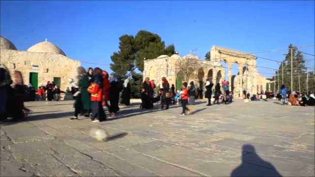 stockvideo's en b-roll-footage met a clown gives balloons to palestinian children in front of dome of the rock during the 1445th anniversary of the birthday of prophet mohammad mawlid... - rotskoepel