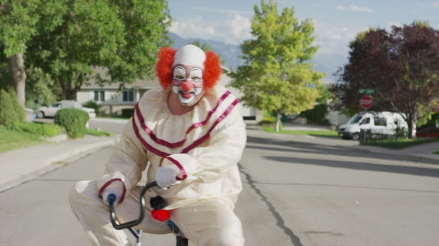 clown riding and waving on awkward small bicycle on neighborhood street / cedar hills, utah, united states - uncomfortable stock videos and b-roll footage