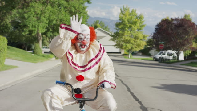 clown riding and waving on awkward small bicycle on neighborhood street / cedar hills, utah, united states - embarrassment stock videos & royalty-free footage