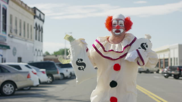 clown running in city street carrying money bags after robbing bank / american fork, utah, united states - humor stock-videos und b-roll-filmmaterial
