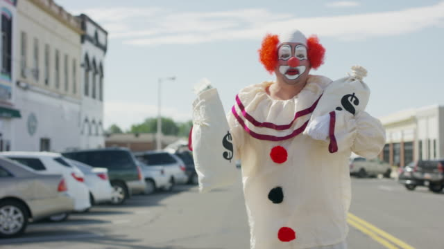stockvideo's en b-roll-footage met clown running in city street carrying money bags after robbing bank / american fork, utah, united states - actrice