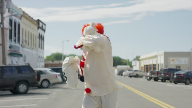 vídeos de stock e filmes b-roll de clown running in city street carrying money bags after robbing bank / american fork, utah, united states - roubo