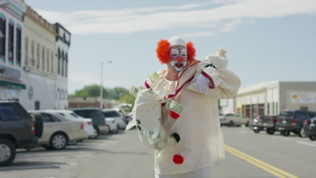 Clown running in city street carrying money bags after robbing bank / American Fork, Utah, United States
