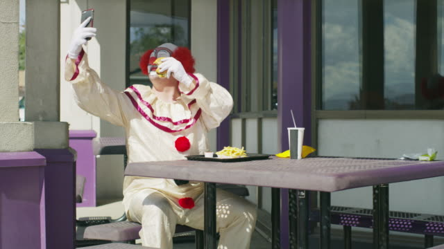 clown sitting and eating fast food while posing for cell phone selfies / pleasant grove, utah, united states - technophile stock videos & royalty-free footage