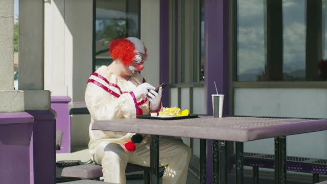 vídeos y material grabado en eventos de stock de clown sitting and eating fast food while texting on cell phone / pleasant grove, utah, united states - paja