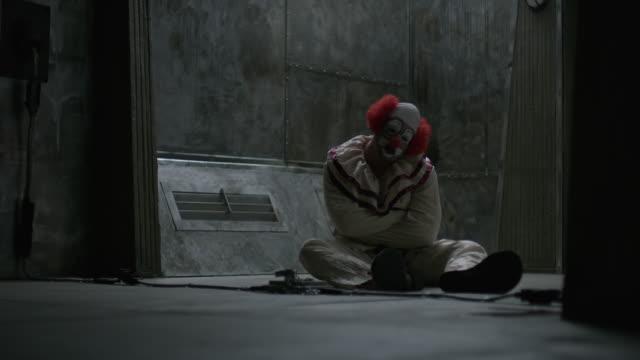 Clown sitting on floor of mental asylum wearing straight jacket / Cedar Hills, Utah, United States
