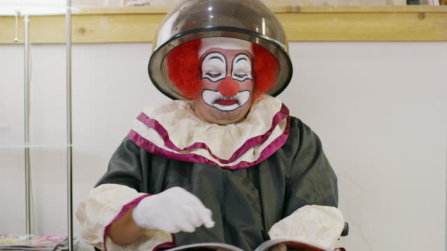 vidéos et rushes de clown sitting under hair dryer at salon reading magazine / pleasant grove, utah, united states - sécher activité