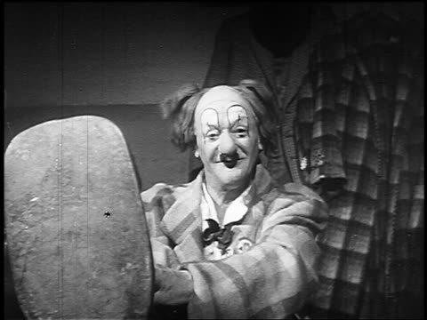 b/w 1955 clown smiling at camera as his hair stands straight up in circus - magic trick stock videos & royalty-free footage