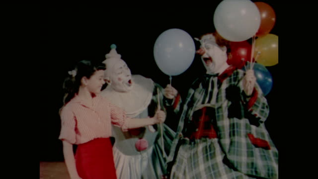 1958 clowns give girl balloon as male audience members laugh - circus stock videos & royalty-free footage