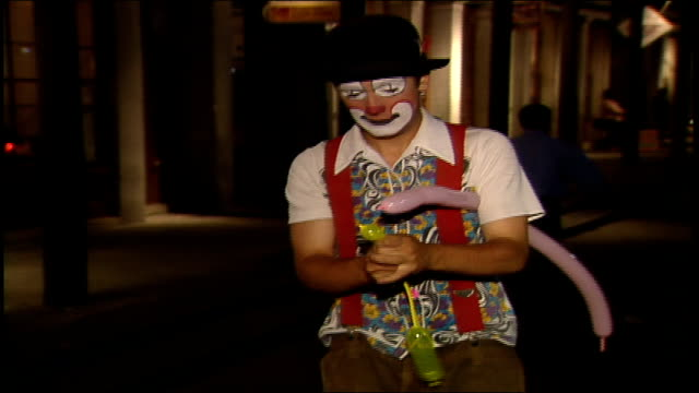 clowns on street at night one juggling the other making balloon animals in new orleans - juggling stock videos & royalty-free footage