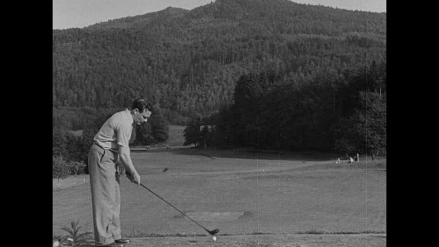 ls clubhouse and grounds / the king's son don juan de borbon and woman walk across golf course / man swings at golf ball / man swings woman carries... - austria flag stock-videos und b-roll-filmmaterial