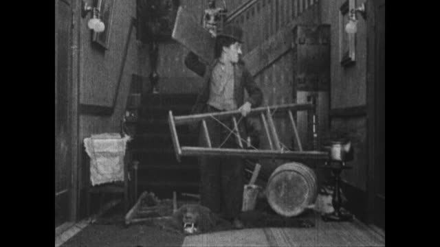 1915 clumsy charlie chaplin irritates mean man as he gathers supplies and accidentally hits man with wood plank - careless stock videos & royalty-free footage