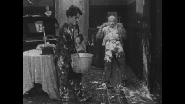 1915 clumsy charlie chaplin uses wallpaper brush to remove paste from fallen man before trying to help him up and throw water over him - sliding stock videos and b-roll footage