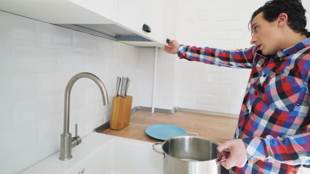vidéos et rushes de homme maladroit essayant de se préparer de la nourriture. - demander