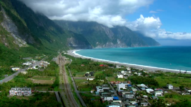 a cluster of buildings and houses border the hualien, taiwan coast. - taiwan stock videos & royalty-free footage