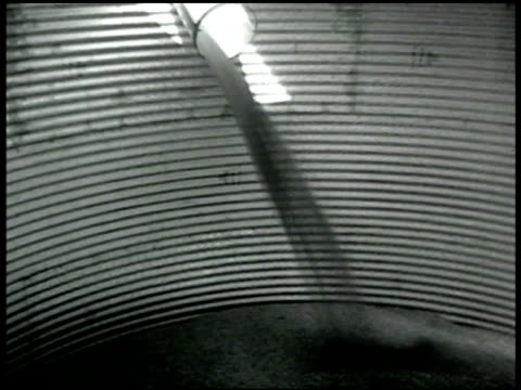 vidéos et rushes de cluster of grainaries wheat grain pouring into grainary cu sign'evernormal grainary' truck driving by row of grainaries - 1936