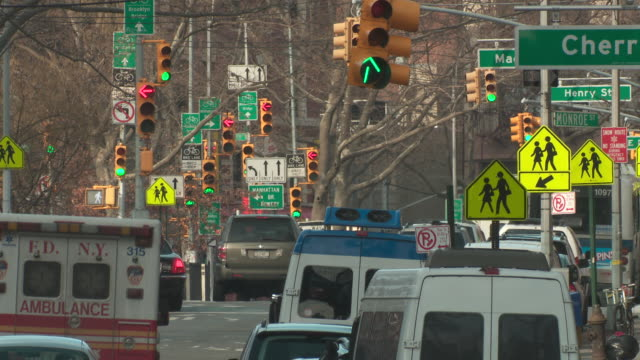 vídeos de stock, filmes e b-roll de a cluster of street signs by the manhattan bridge in new york city.  traffic flows by. - escrita ocidental