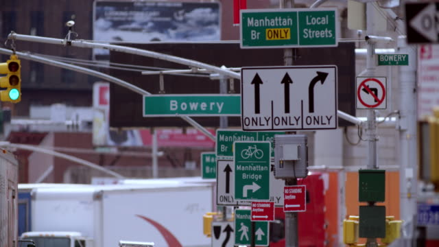 cluster of street signs navigating pedestrians on busy new york city street. - segnaletica stradale video stock e b–roll