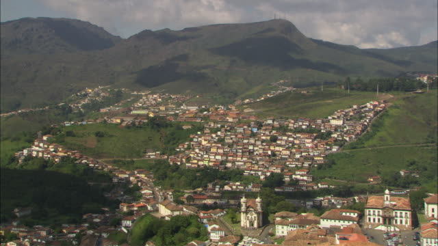 vídeos de stock e filmes b-roll de ha ws clusters of houses in a valley as shadows of clouds pass over them/ ouro preto, brazil - preto