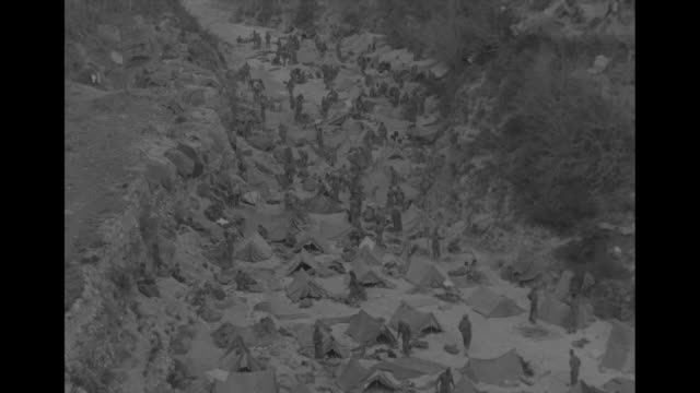 ms clusters of villages in mountainous italian countryside building in foreground is damaged / ms riverbed with soldiers and about 75 tents set up in... - グリルパン点の映像素材/bロール
