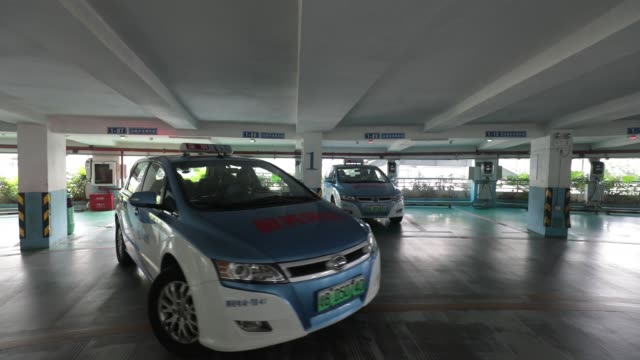 stockvideo's en b-roll-footage met co. e6 electric taxis charge at stations in a parking lot tower at the company's headquarters in shenzhen, china, on thursday, sept. 21, 2017 - toonzaal