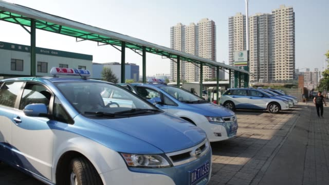 vídeos de stock, filmes e b-roll de byd co e6 electric taxis stand while being charged at a state grid corp of china charging station in taiyuan shanxi province china on tuesday sept 13... - posto de carregamento de veículos elétricos