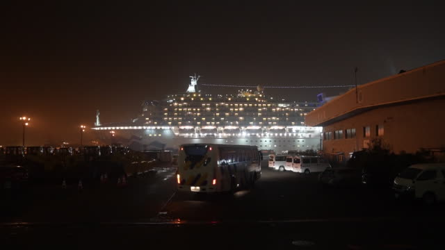 coach and an ambulance travel towards the diamond princess cruise ship, operated by carnival corp., docked at dusk in yokohama, japan, on sunday,... - cruise stock videos & royalty-free footage