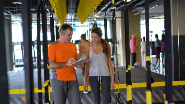 Coach and female customer walking and talking between the suspension straps at the gym