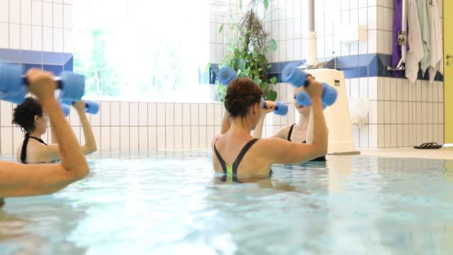 Coach en vrouwtjes oefenen met gewichten in zwembad
