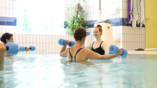 Coach and women exercising with dumbbells in pool